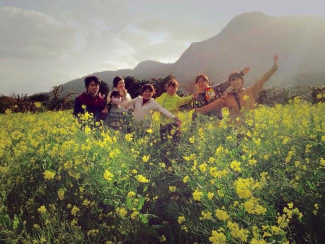 村おこしボランティア【宝島コース】で菜の花畑で記念撮影する学生ボランティア